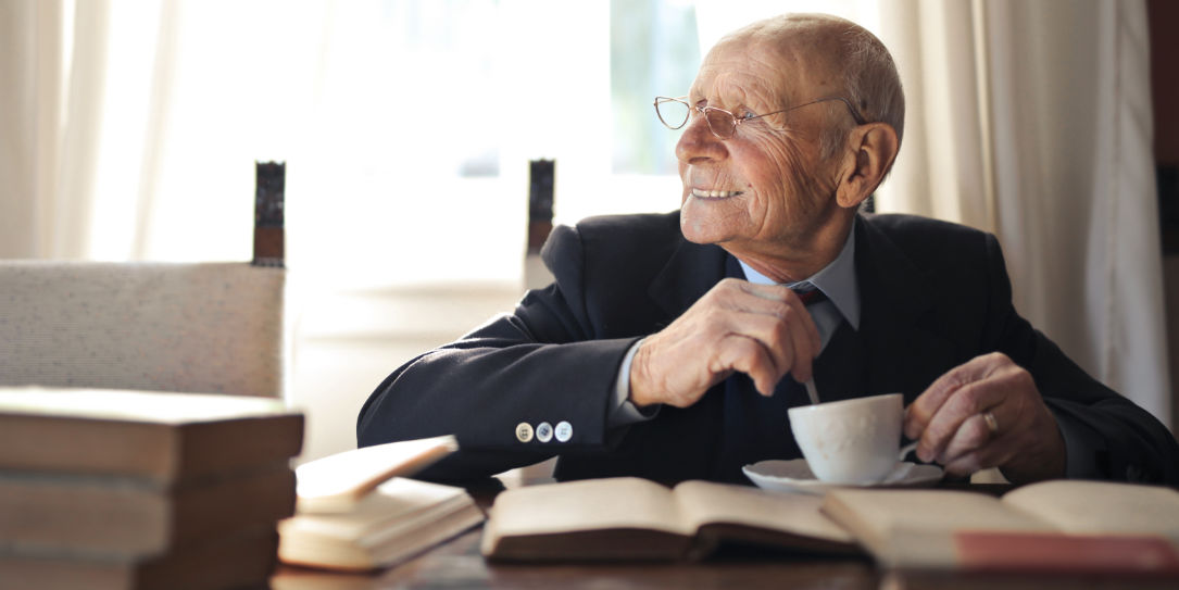 old dude drinking coffee and reading some books looking all happy and what not